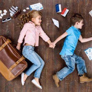 Happy children. Top view creative photo of little boy and girl on vintage brown wooden floor. Children lying near travel things. Girl with suitcase